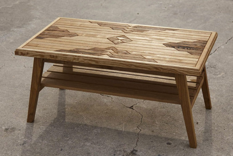A wooden table made by a craftsman bag brand featuring a native pattern.